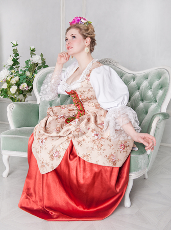 Beautiful woman in old-fashioned historic medieval dress on the sofa