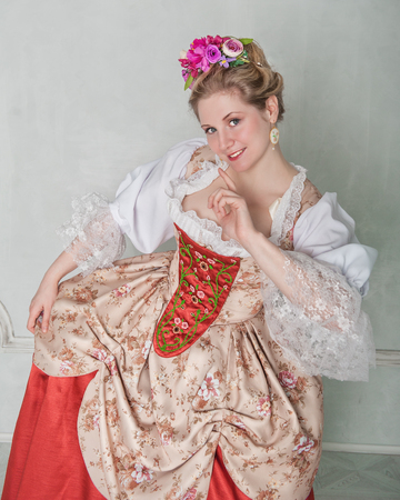 Beautiful woman in old-fashioned historic medieval dress smiling
