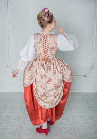 Beautiful woman in old-fashioned historic medieval dress. Back pose Stock Photo