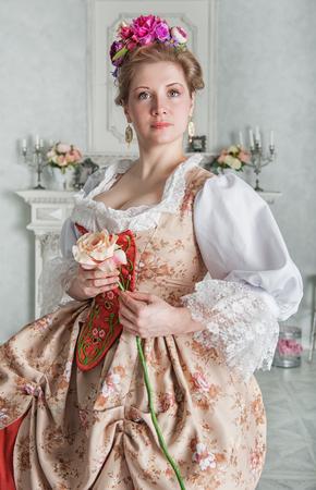 ピンクのバラを保持している中世のドレスを着た美しい女性