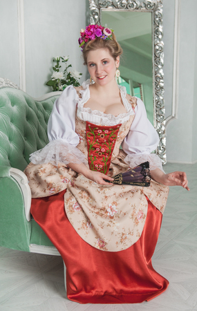 the magnificent: Beautiful woman in old-fashioned historic medieval dress on the sofa