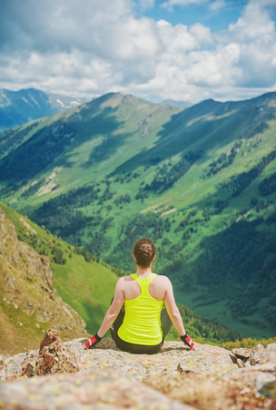 Woman doing relax exercise on the top of mountain outdoor photo