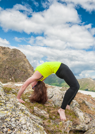 Woman doing exercise on the top of mountain outdoor photo