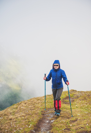 Tourist woman hiker walking in fog on the top of mountain outdoor photo