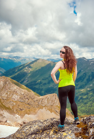 Woman hiker standing on the top of mountain outdoor photo