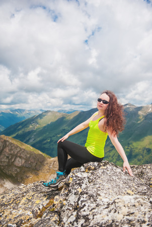 Woman hiker sitting on the top of mountain outdoor photo