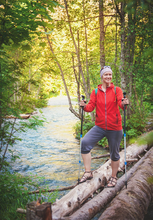 Woman hiker with sticks walking in forest outdoor. Tourism concept