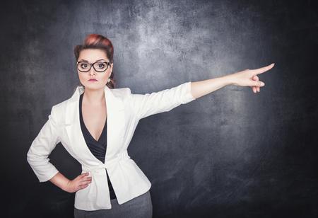 深刻な女性教師が黒板黒板背景に指摘