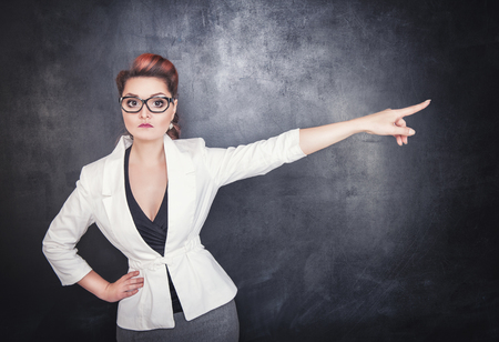 Serious woman teacher pointing out on chalkboard blackboard background