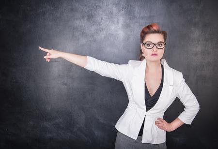 Professeur de femme sérieuse soulignant l'arrière plan du tableau noir Banque d'images - 83372544