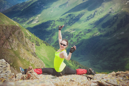 Happy Woman doing exercise on the top of mountain outdoor photo