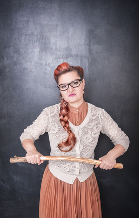 Strict teacher with wooden stick on the chalkboard blackboard background