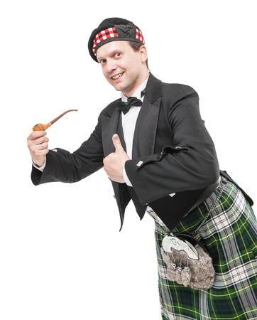 Scottish man in traditional national costume with smoking pipe isolated