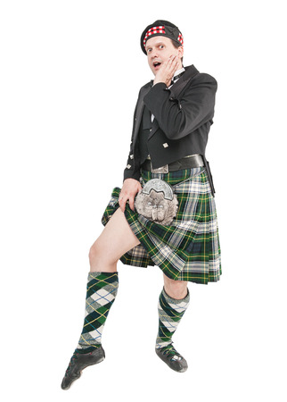 Scottish man in traditional national costume showing leg isolated