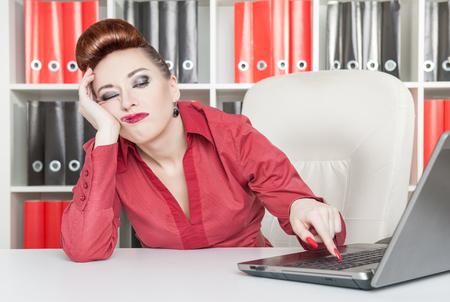컴퓨터와 사무실에서 일하는 지루한 사업 여자