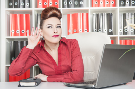 Beautiful business woman eavesdropping working in office