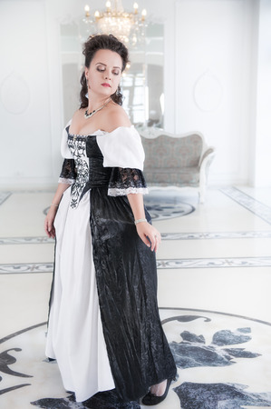 Beautiful young woman in black and white long medieval dress