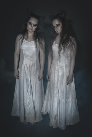 Two terrible ghost with horns on dark background