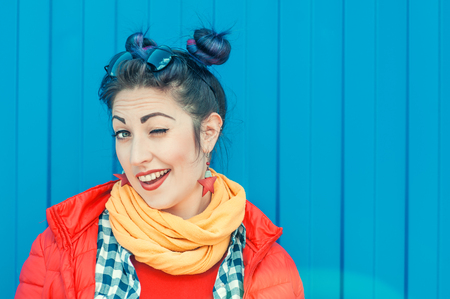 Young beautiful fashion hipster woman with colorful hair winking over wall background