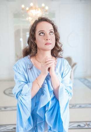 Young beautiful woman in old-fashioned negligee praying