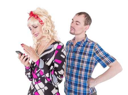 Jealous husband watching his wife using mobile phone. Couple conflict Stock Photo