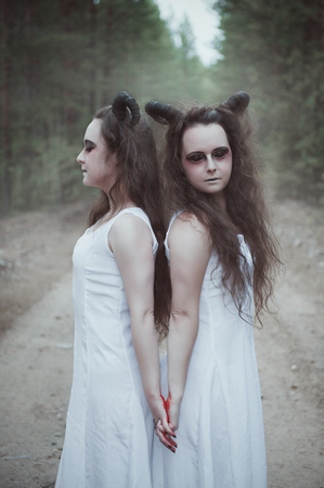 Two twins demons with horns in forest outdoor Stock Photo