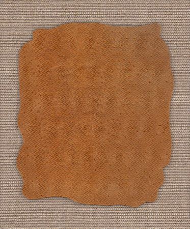 Piece of leather on the fabric linen textile texture background