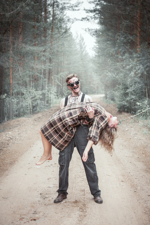 Cannibal steampunk Man with ax and his victim in forest outdoor Stock Photo