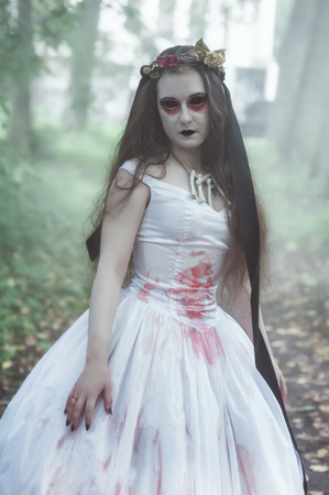 Creepy dead bride in white dress. Halloween scene