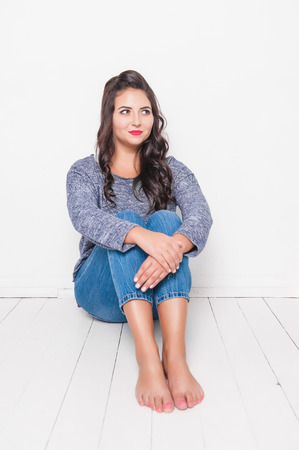 Beautiful smiling plus size woman barefoot sitting on the floor. Body positive concept