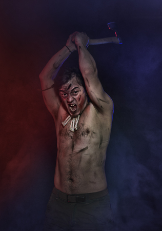 Terrible man with axe screaming in red and blue fog. Halloween scene Archivio Fotografico