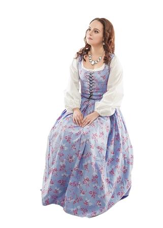 Mujer hermosa joven en vestido largo medieval sentado aislado en blanco Foto de archivo