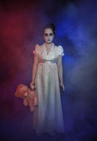 Beautiful ghost woman in white victorian dress with teddy bear. Halloween scene