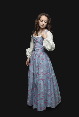 Young beautiful woman in long medieval dress on dark background