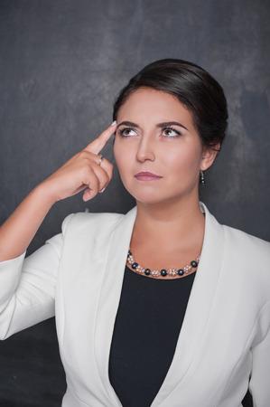 Beautiful woman with finger to her head on chalkboard blackboard background