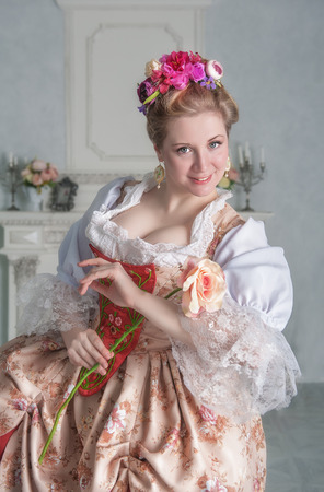 Beautiful young smiling woman in medieval dress holding pink rose Zdjęcie Seryjne - 122762595