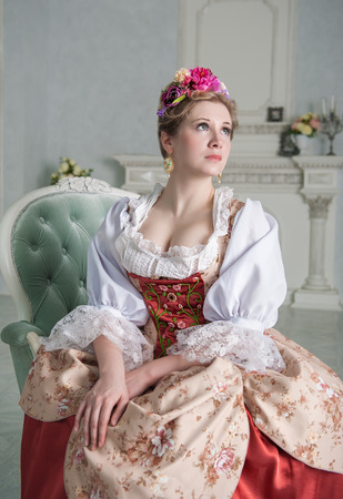 Beautiful woman in old-fashioned historic medieval dress on the sofa Zdjęcie Seryjne - 122762596