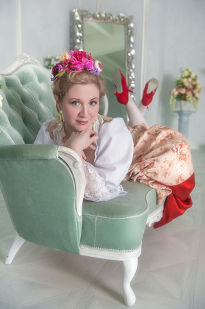 Beautiful woman in old-fashioned historic medieval dress on the sofa Zdjęcie Seryjne - 122762602