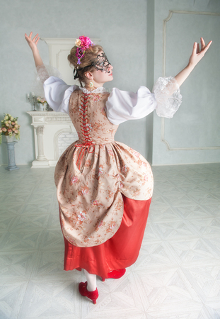 Beautiful woman in old-fashioned historic medieval dress with mask dancing Zdjęcie Seryjne - 122762600