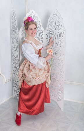 Beautiful woman in old-fashioned medieval dress holding pink rose Zdjęcie Seryjne - 122762607