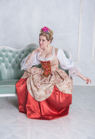 Beautiful woman in old-fashioned historic medieval dress on the sofa Zdjęcie Seryjne - 122762612