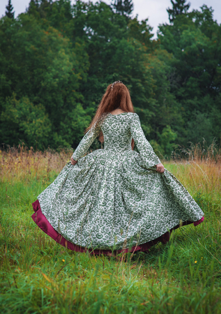 Beautiful woman in long medieval dress dancing outdoor