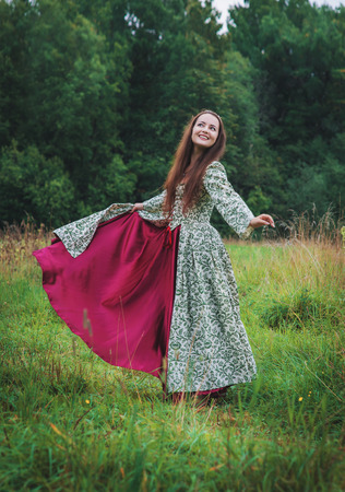 Beautiful happy woman in long medieval dress dancing outdoor