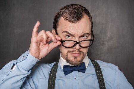 Handsome strict teacher in eyeglasses looking at you on blackboard background