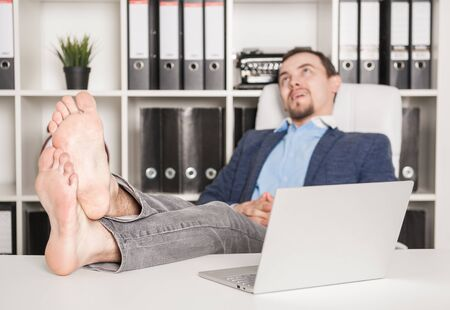 Handsome barefoot business man relaxing in office. Focus on legs