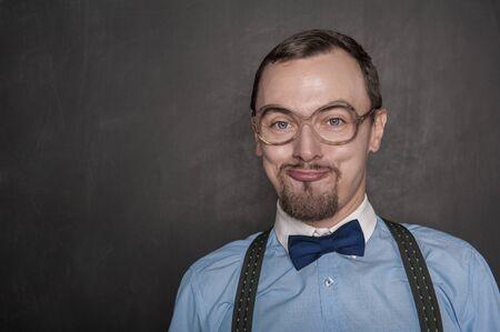Funny teacher in eyeglasses smiling on blackboard background