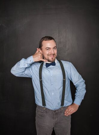 Handsome business man with call gesture on blackboard background
