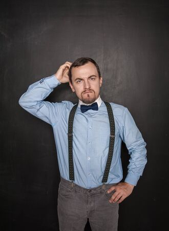 Handsome business man scratching his head on blackboard background