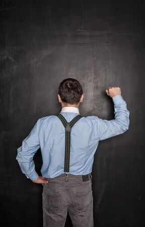 Business man knock by fist on blackboard background. Opportunity concept