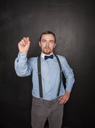 Handsome business man touch something on blackboard background